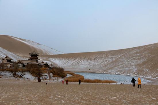 2020年12月8日,游客在敦煌市鸣沙山月牙泉景区欣赏雪景。