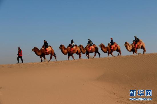 12月1日,游客在甘肃省敦煌市鸣沙山月牙泉景区游览。
