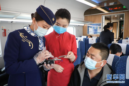 12月16日,兰州客运段乘务员(左一)与东航甘肃分公司乘务员(左二)在C8502次列车上交流验票业务。新华社记者 马希平 摄