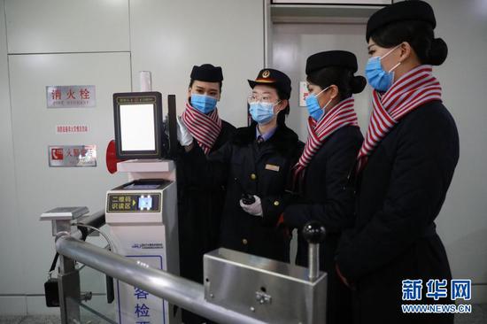 12月16日,在中国铁路兰州局集团有限公司中川机场站,一名客运员(左二)与东航甘肃分公司乘务员交流业务。新华社记者 马希平 摄
