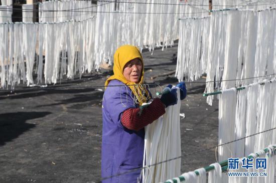 12月23日,甘肃省定西市安定区宁远镇红土村的村民在晾晒粉条。新华社发(王克贤 摄)
