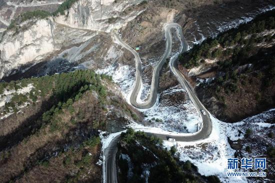 12月24日,民警驾车在陇南市武都区积雪山路上巡逻(无人机照片)新华社记者 郎兵兵 摄。