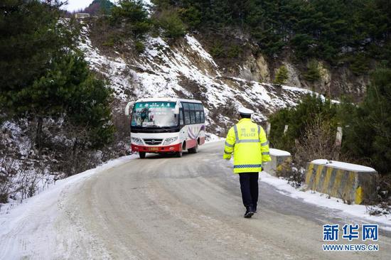 12月24日,民警在陇南市武都区积雪山路上巡逻。新华社记者 郎兵兵 摄
