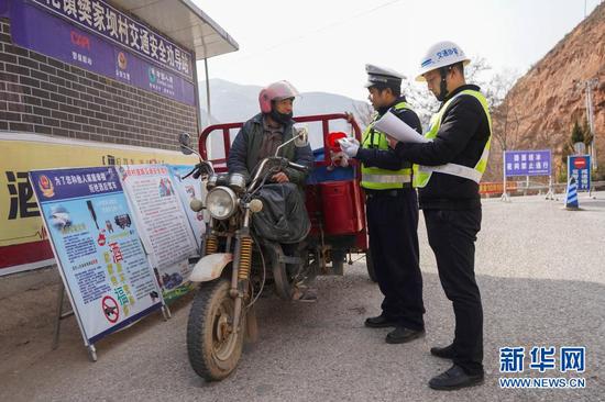 12月24日,在陇南市武都区安化镇樊家坝村,民警对过往三轮车进行安全检查。新华社记者 郎兵兵 摄