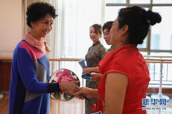 12月24日,兰州老年大学模特二班举办迎新春汇报表演,李玲(左一)给学员颁奖。新华社记者 马希平 摄