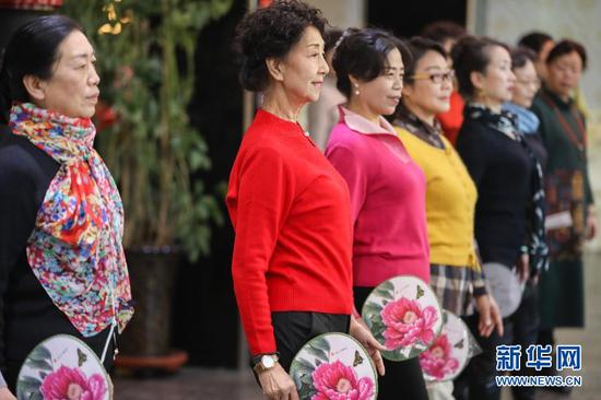 12月23日,在甘肃省兰州市一酒店多功能厅,李玲(左二)带领学员们练习模特步。新华社记者 马希平 摄