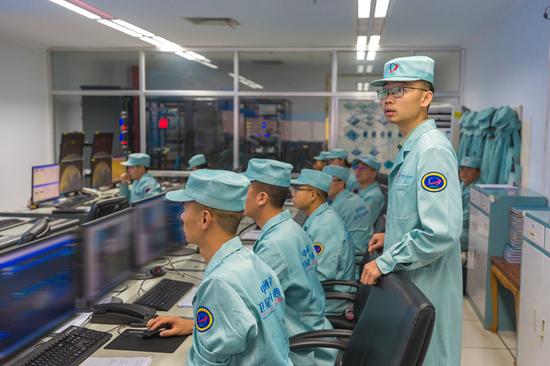 酒泉卫星发射中心指挥显示操控组组员在执行试验六号02星任务,组长曾显华(右一)密切关注图像的显示状态(7月5日摄)。新华社发(杨智健 摄)