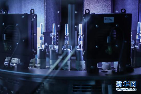 12月25日,在国药集团中国生物北京生物制品研究所的新冠病毒灭活疫苗分包装车间内,疫苗产品在灯检机内进行灯检。新华社记者 张玉薇 摄