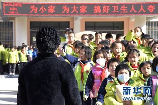 2020年12月24日,在东乡族自治县实验小学校门口,牟阿西也等待孩子放学。新华社记者 王朋 摄