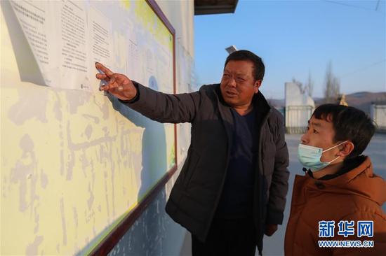 1月5日,在会宁县韩家集镇袁家坪村村委会,任长太(左)和村干部交流工作。新华社记者 马希平 摄
