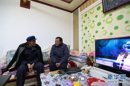 1月5日,在会宁县韩家集镇袁家坪村,任长太(右)在村民家走访。 新华社记者 马希平 摄