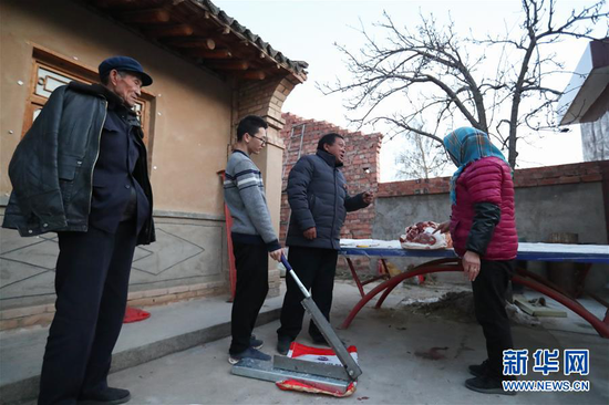 1月5日,在会宁县韩家集镇袁家坪村,任长太(右)在村民家和村民沟通。新华社记者 马希平 摄