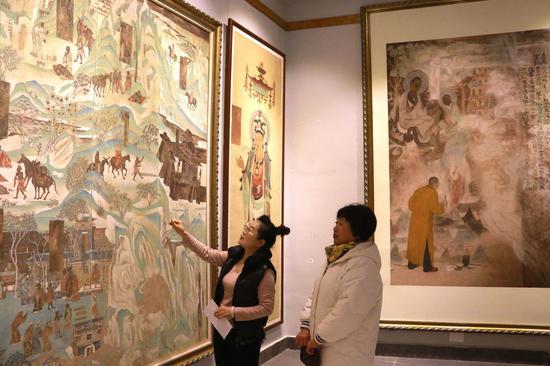 """1月6日,""""敦煌石粉彩绘技艺""""酒泉市级非物质文化遗产代表性传承人王亚林在甘肃省敦煌市月牙泉镇的工作室里,向参观者介绍自己临摹创作的敦煌壁画作品。"""