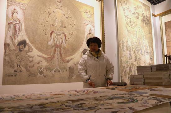 """1月6日,在""""敦煌石粉彩绘技艺""""酒泉市级非物质文化遗产代表性传承人王亚林的工作室里,参观者参观王亚林临摹创作的敦煌壁画作品。"""