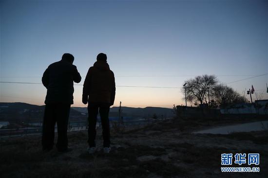 1月5日,在会宁县韩家集镇袁家坪村,任长太(左)和村干部巡查。新华社记者 马希平 摄