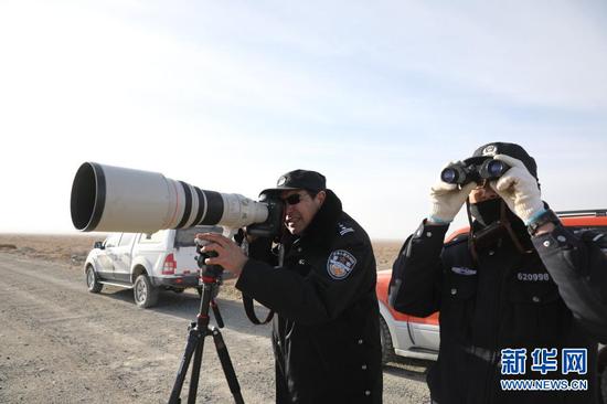 1月8日,安南坝分局民警海拉提(左)和阿尔根别克·阿海观察记录野生动物活动情况。新华社记者 杜哲宇 摄
