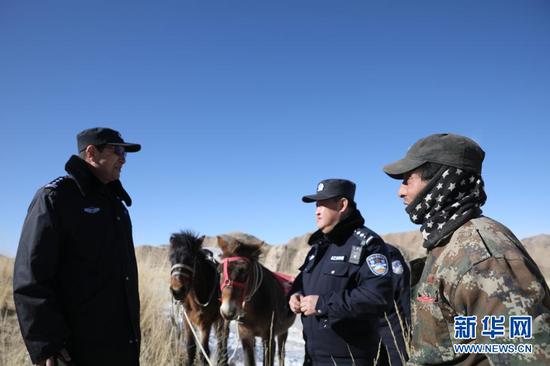 1月8日,安南坝分局民警向牧民了解野生动物迁徙情况。新华社记者 杜哲宇 摄