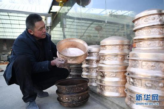 1月16日,在甘肃省定西市岷县清水镇清水村,岷县铜铝铸造技艺代表性传承人蒋胜平在查看铸造出来的成品。新华社记者 陈斌 摄