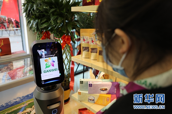 """顾客和""""甘味""""农产品展销直播中心内的机器人交流。新华网(王生元 摄)"""