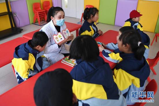 1月15日,岷县妇女儿童康养中心康复治疗师陈蓉蓉带领孩子们开展语言康复训练。新华社记者 陈斌 摄