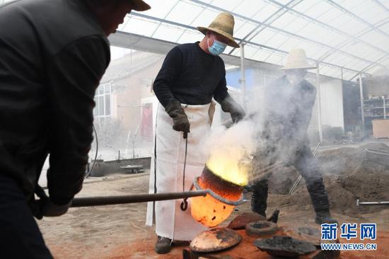 1月16日,在甘肃省定西市岷县清水镇清水村,岷县铜铝铸造技艺代表性传承人蒋胜平(中)和同伴在浇铸一件铜制品。新华社记者 陈斌 摄