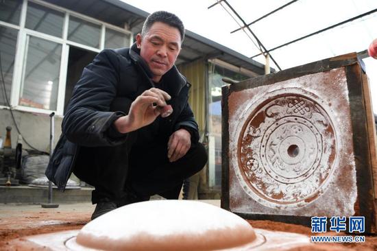1月16日,在甘肃省定西市岷县清水镇清水村,岷县铜铝铸造技艺代表性传承人蒋胜平在刚制成的模具上盖上自己的印章。新华社记者 陈斌 摄
