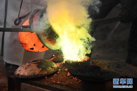 1月16日,在甘肃省定西市岷县清水镇清水村,匠人们在浇铸一件铜制品。新华社记者 陈斌 摄