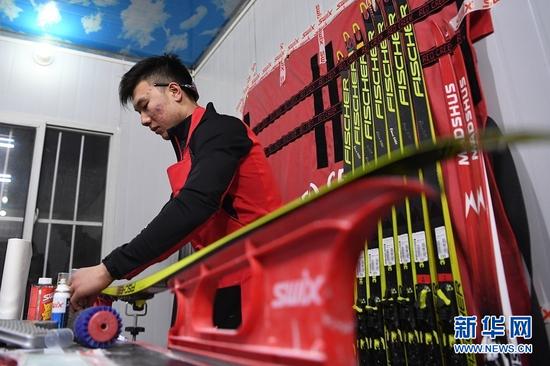 1月22日晚,打蜡师王啸在打蜡房给雪板打蜡。新华社记者 陈斌 摄