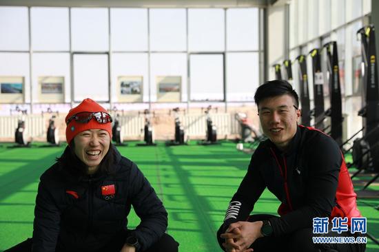 1月23日,打蜡师王啸(右)和越野滑雪国家集训队队员李馨交流比赛中的雪板情况。新华社记者 杜哲宇 摄