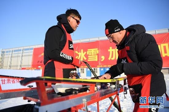 1月23日,打蜡师王一涵(左)和泰利尔在检查运动员的雪板。 新华社记者 陈斌 摄