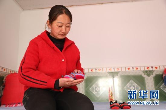 华池县南梁镇高台村村民张应芬拿着她给邱军的孩子做的布鞋(1月23日摄)。新华社记者 马莎 摄