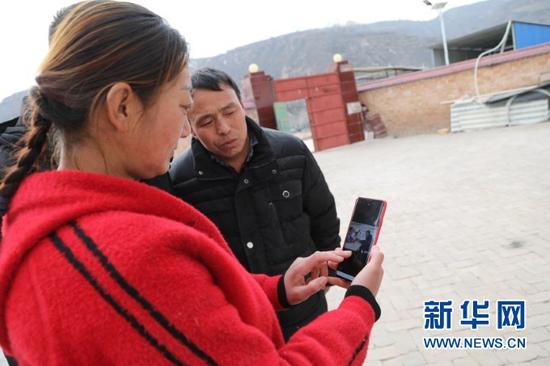 华池县南梁镇高台村村民张应芬与家人翻看邱军的照片(1月23日摄)。新华社记者 马莎 摄