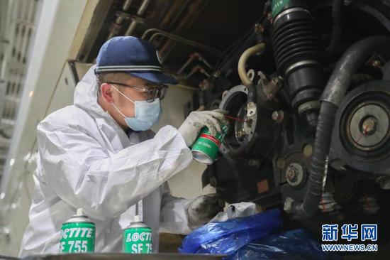 1月27日,在中国铁路兰州局集团有限公司兰州车辆段兰州西动车运用所,工作人员清洗动车组轴端。新华社记者 马希平 摄