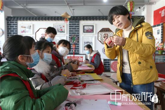 孩子们跟老师学习剪纸。