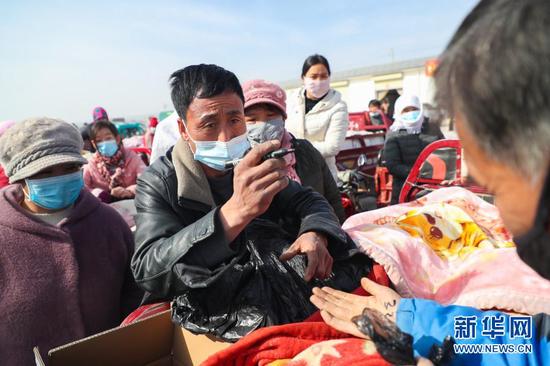 2月4日,在靖远县北湾镇新坪村农贸市场,菜贩胡荣辉同菜农商议黄瓜价格。新华社记者 马希平 摄
