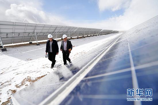 两名技术人员从光伏发电场内走过。新华社记者 陈斌 摄(资料图片)
