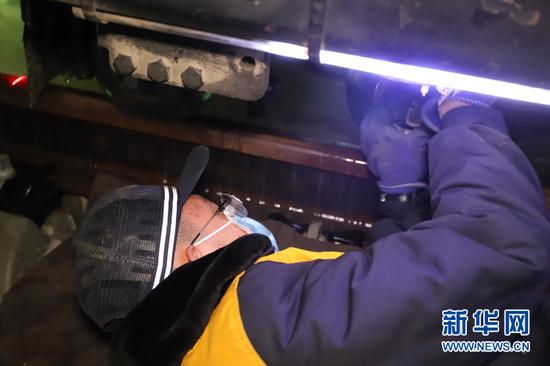 钢轨探伤工躺在寒冷的地面上,在寒风中更换探轮。新华网发(俱娜 摄)