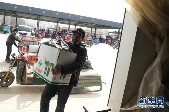 2月4日,在靖远县北湾镇新坪村农贸市场,菜农在搬运黄瓜。新华社记者 马希平 摄