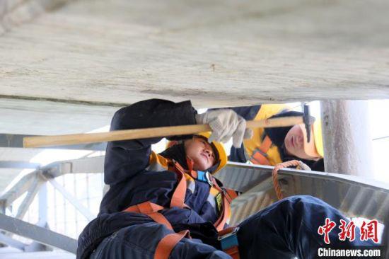 """图为""""90后""""工长王春瑶躺着和同事检查拱底空响掉块。 王光辉 摄"""