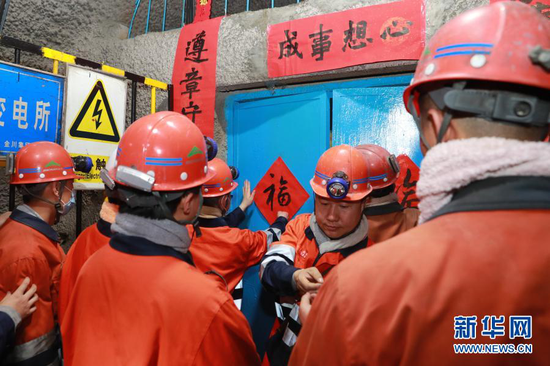 2月11日,在金川集团三矿区采矿二工区,工人们一起贴春联和福字。新华社记者 杜哲宇 摄