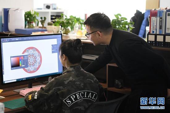 马成虎(右)和同事一起设计敦煌元素文创产品(1月14日摄)。新华社记者 陈斌 摄