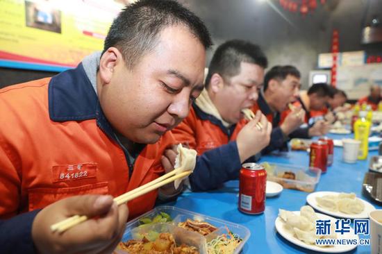2月11日,在金川集团三矿区采矿二工区井下食堂,工人们一起吃年夜饭。新华社记者 杜哲宇 摄