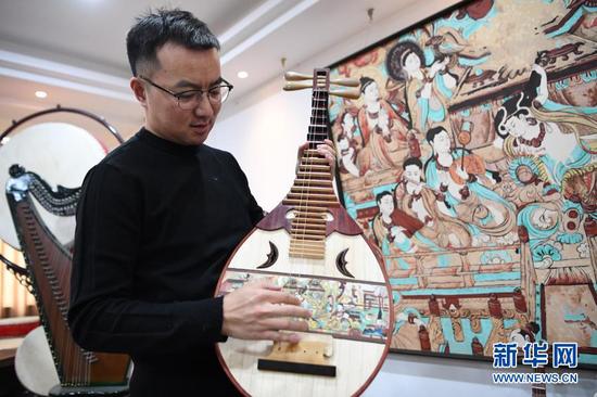 马成虎在介绍复原的敦煌壁画乐器(1月14日摄)。新华社记者 陈斌 摄