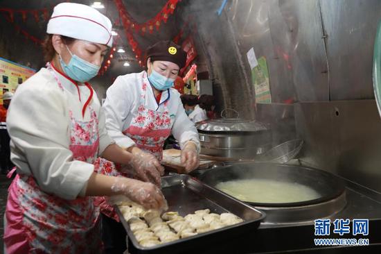 2月11日,在金川集团三矿区采矿二工区井下食堂,后勤服务人员为工人下饺子。新华社记者 杜哲宇 摄