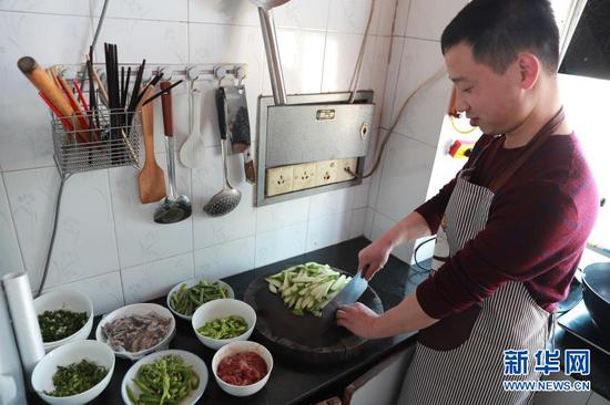2月12日,陈林在家给妻子孩子做饭。新华社记者 杜哲宇 摄