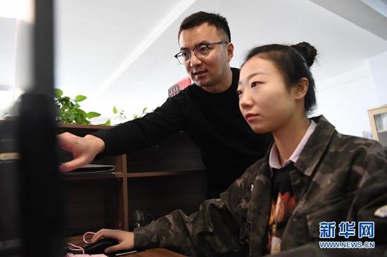马成虎(左)和同事一起设计敦煌元素文创产品(1月14日摄)。35岁的马成虎是甘肃丝绸之路文创工场的总经理。新华社记者 陈斌 摄