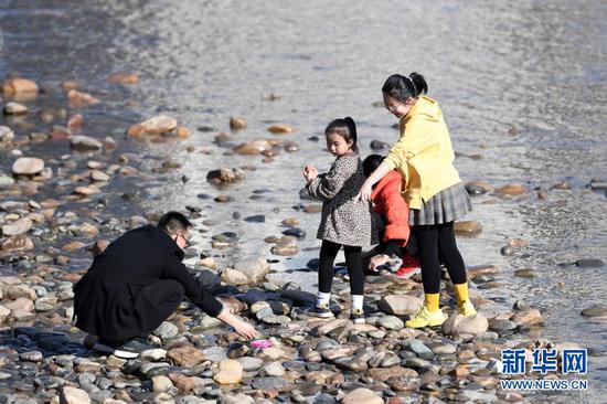 2月18日,市民带着孩子在黄河兰州段河床上捡石头。新华社记者 范培珅 摄