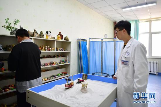 柳伟(右)和患者进行心理沙盘游戏(1月11日摄)。新华社记者 陈斌 摄