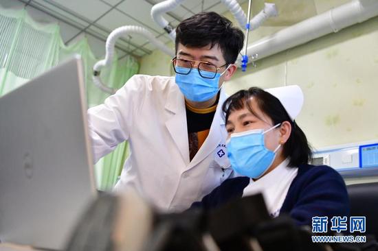 柳伟(左)和同事交流治疗方案(1月11日摄)。新华社记者 陈斌 摄