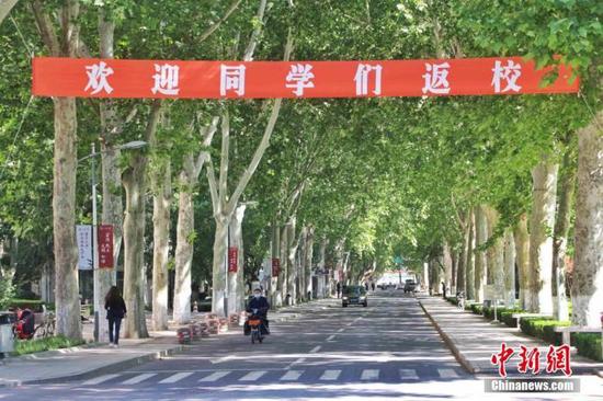 """资料图:2020年5月,某高校校园内悬挂""""欢迎同学们返校""""的横幅。 赵晓 摄"""
